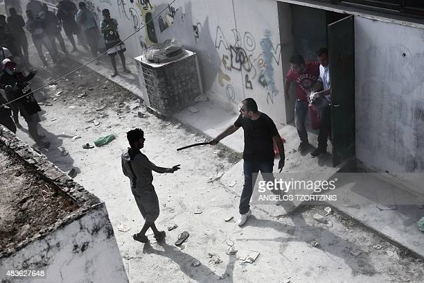 A policeman confronts a migrant with a truncheon during a registration procedure at the stadium on the Greek island of Kos on August 11 2015 Police...