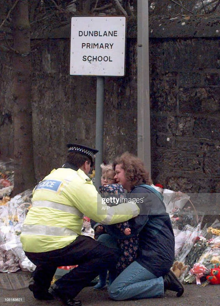 A policeman consoles a mother and her children after they had laid a bouquet of flowers outside the primary school 15 March where gunman Thomas Hamilton shot and killed 16 children and their teacher on 14 March in Dunblane. Hamilton commited suicide after the shooting.