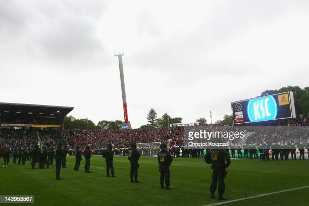 Policeman control the fans after the Second Bundesliga match between Karlsruher SC and Eintracht Frankfurt at Wildpark stadium on May 6 2012 in...