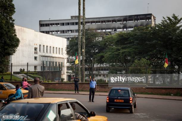 A policeman controls traffic in front of the damaged building of Cameroon's parliament on November 17 2017 in Yaounde after a fire swept through the...