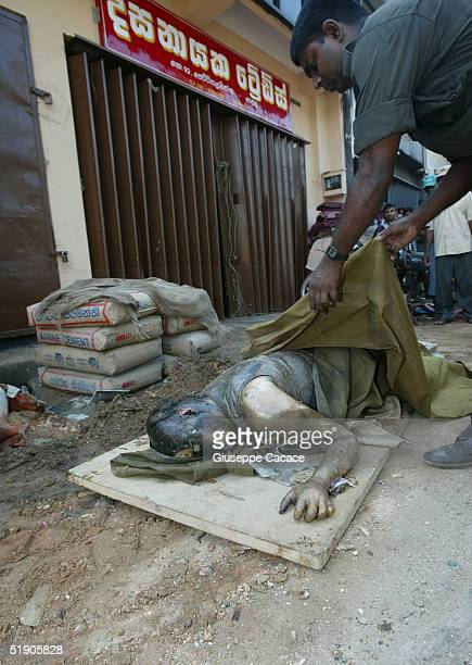Policeman covers the body of a tsunami victim found inside a shop in the central market December 31, 2004 in Galle, Sri Lanka. The death toll from...