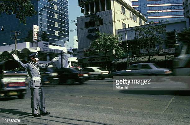 policeman directing traffic with anti pollution mask: thailand