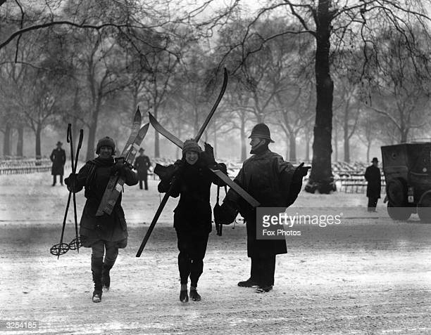 A policeman directs the Misses Debenham across a snowcovered road in Hyde Park where they are hoping to use their skis