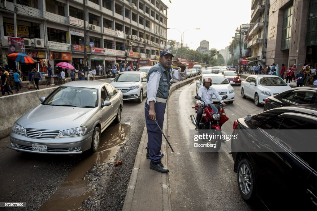 A policeman directs traffic from the central reservation of a road in the Gulshan area of Dhaka, Bangladesh, on Wednesday, June 6, 2018. The Bangladesh economy will expand 6.9% this financial year and 6.8% in 2019, according to a survey conducted by Bloomberg News. Photographer: Ismail Ferdous/Bloomberg via Getty Images
