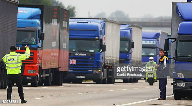 A policeman directs trucks as they queue on the M20 on September 12 2008 near Folkestone EnglandA fire which broke out yesterday on a freight train...