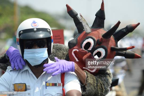Policeman dressed up as demon resembling the Covid-19 coronavirus takes part with other policemen in a Covid-19 coronavirus awareness rally in...