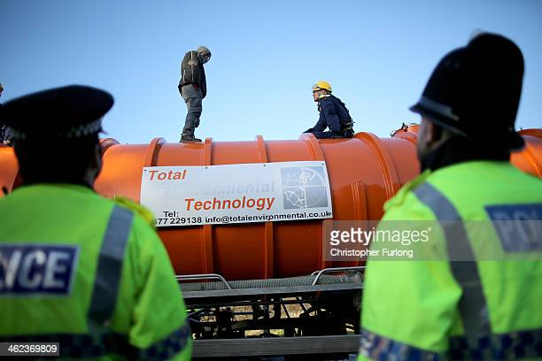 A policeman edges his way towards an antifracking protestor standing on the top of a truck carrying chemicals to the Barton Moss gas fracking...
