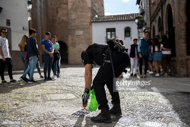 A policeman empties beer into a gutter To drink alcohol was forbidden in Plaza Larga Square during El día de la Cruz or Día de las Cruces is one of...