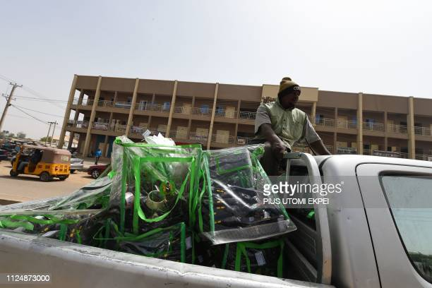 A policeman escorts election card readers and ballot boxes to the headquarters of the Independent National Electoral Commission in Kano Nigeria on...