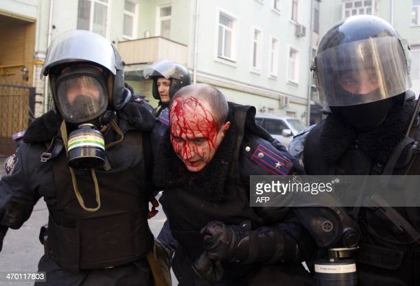 Policeman evacuate a wounded colleague during clashes with antigovernment protesters in Kiev on February 18 2014 Ukrainian antigovernment protestors...