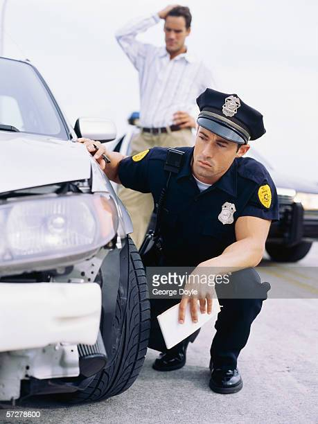 Policeman examining a car involved in an accident
