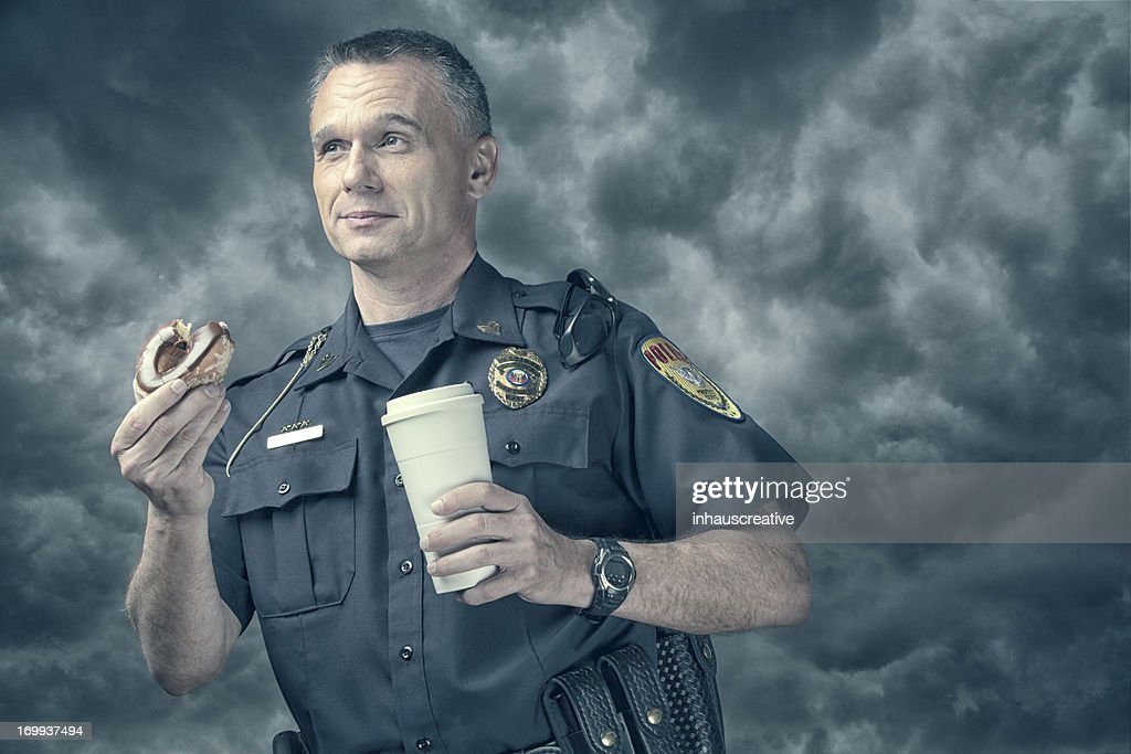 Policeman excited about his donut and coffee break : Stock Photo