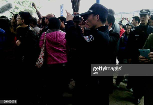 A policeman films as demonstrators call for press freedom in support of journalists from the Southern Weekend newspaper outside the company's office...