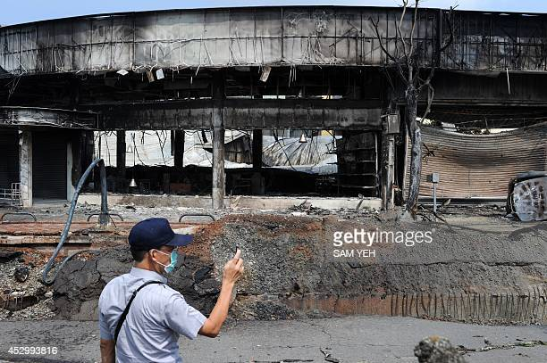 A policeman films the site of a gas explosion in the southern Taiwan city of Kaohsiung on August 1 2014 A series of powerful gas blasts killed at...