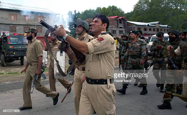 A policeman fires a teargas shell to disperse protesters after a cab was hit by an Indian Army vehicle killing at least six people July 16 2014 in...
