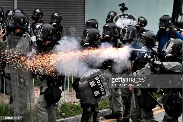 TOPSHOT A policeman fires tear gas to disperse protesters during a demonstration in the district of Yuen Long in Hong Kong on July 27 2019 Hong Kong...