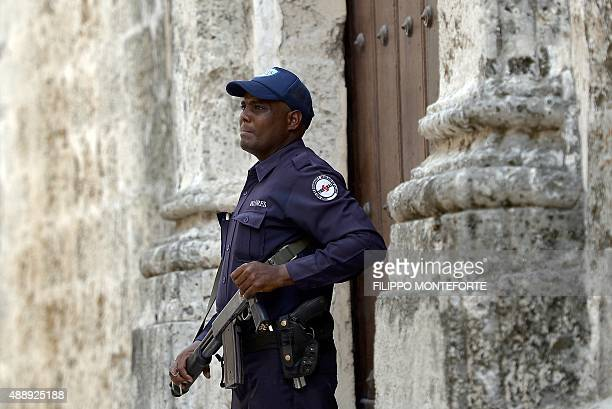 A policeman from a special unit that custodies securities stands guard by a side door of Havana's Cathedral a day before Pope Francis' arrival in...