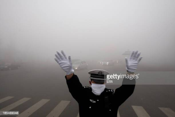 A policeman gestures as he works on a street in heavy smog in Harbin northeast China's Heilongjiang province on October 21 2013 Choking clouds of...