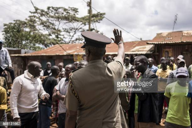 A policeman gestures to supporters of Kenyan opposition leader gather during a standoff with the police in Kawangware outside Gatina primary school...