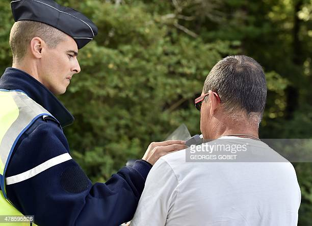A policeman gives a contravenor a breathalyser test during a roadside check focused on speed near Nantes on June 26 2015 Speed control operations...