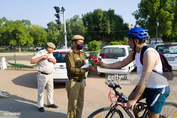 A policeman gives a rose to a cyclist in a bid to inspire him to stay home during a oneday Janata curfew imposed as a preventive measure against the...