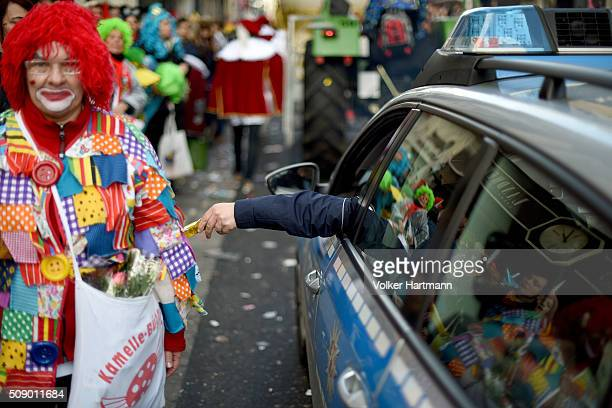Policeman gives a sweet to a carnival reveller during the annual Rose Monday parade on February 8 2016 in Cologne Germany The centuriesold tradition...