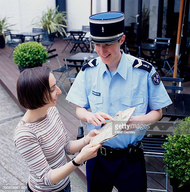 policeman giving directions to woman, smiling, elevated view - french culture stock pictures, royalty-free photos & images