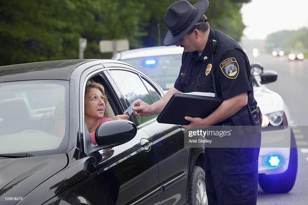 Policeman giving driver speeding ticket : Stock Photo