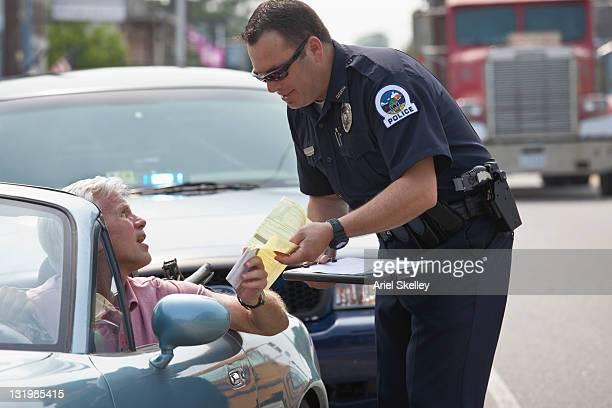policeman giving driver traffic citation - penalty fotografías e imágenes de stock
