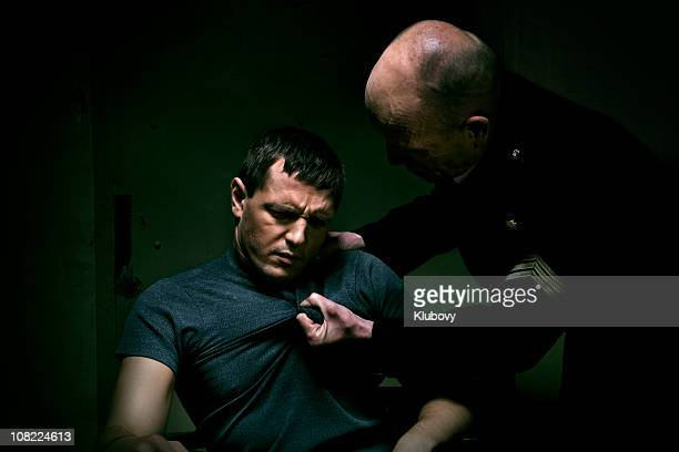 Policeman grabbing man's tshirt during interrogation