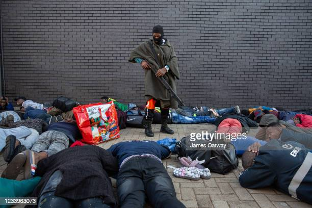 Policeman guards a group of suspected looters who were apprehended at a shopping centre on July 13, 2021 in Vosloorus, Johannesburg, South Africa....