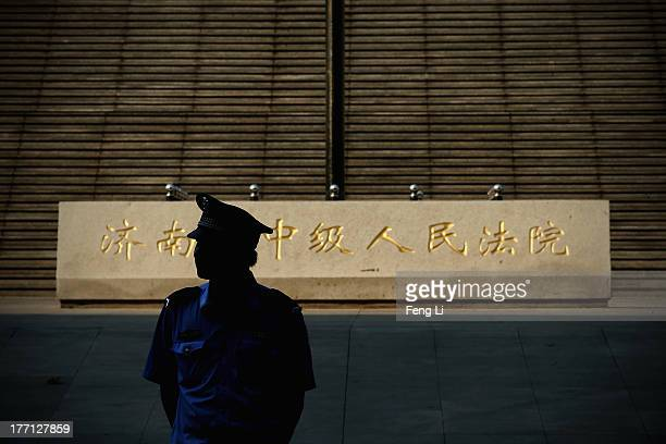 A policeman guards outside the Jinan Intermediate People's Court on August 21 2013 in Jinan China Chinese authorities will issue formal charges...