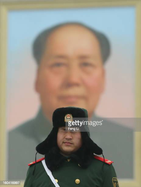 A policeman guards with uncomfortable expression in front of a giant portrait of the late chairman Mao Zedong at the Tiananmen Square during severe...