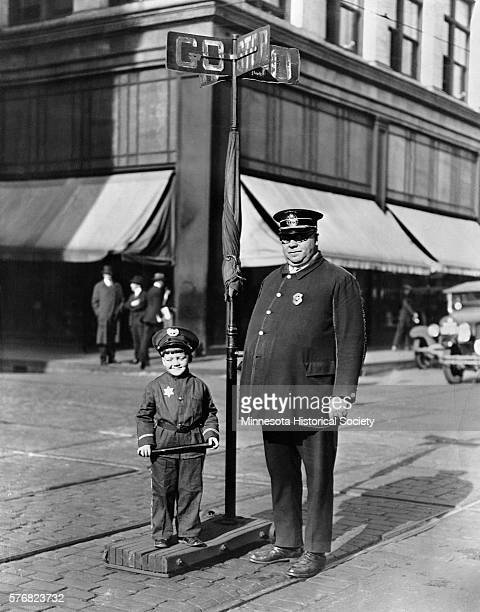 Policeman Hans Offerdahl with an appropriately attired young sidekick operates a handcontrolled traffic signal at an intersection