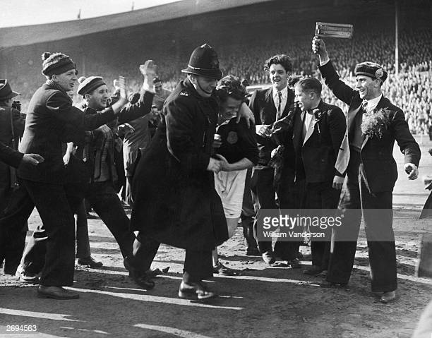 Policeman helping the Glasgow Rangers stalwart and Scotland captain, George Young, from the pitch after Scotland beat England 3-1 at Wembley....