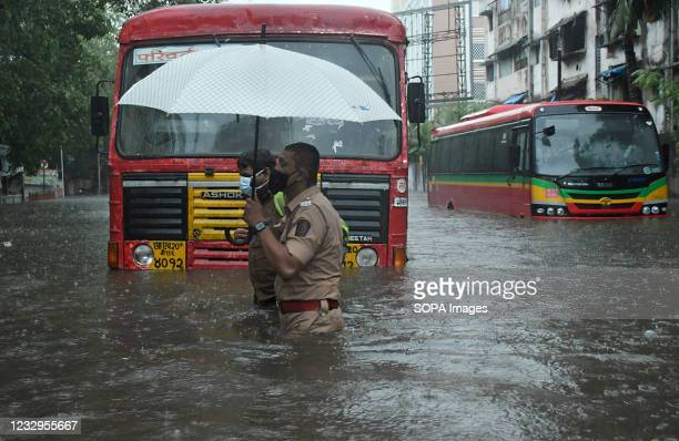 Policeman helps a public transport driver to cross a flooded street due to heavy rain caused by cyclone 'Tauktae' in Mumbai. Strong winds and heavy...