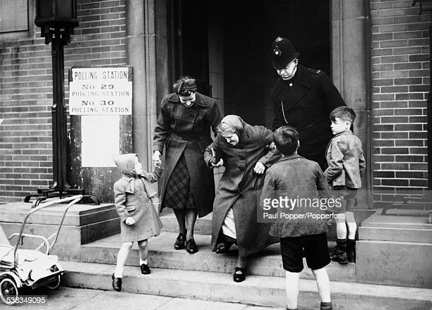 Policeman helps an elderly lady down the steps of the polling station in Lower Broughton, Salford, during the General Election, 25th October 1951.