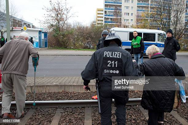 A policeman helps elderly people to cross tracks during a protest against the pending construction of a new center to house refugees in Marzahn...