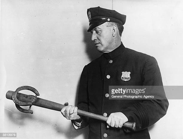A policeman holding a baseball bat with a horseshoe attached to the end It is one of the exhibits in the crime museum at New York's Police College