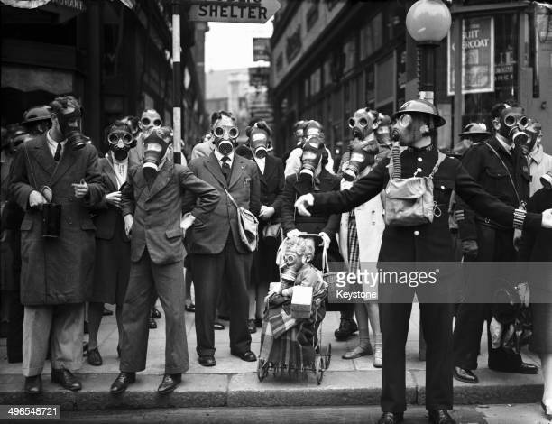 A policeman holding up pedestrians during a gas drill in Richmond Surrey 31st May 1941 The drill involved a canister of tear gas to simulate a gas...