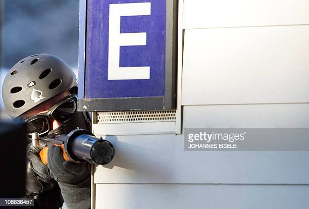 A policeman holds a rubberbullet gun as he stands guard near the Congress Hall during a demonstration held to protest against the World Economic...