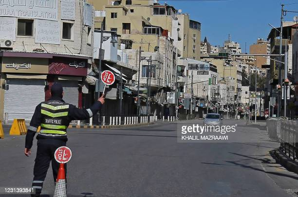 Policeman holds a stop sign in an almost deserted avenue in the Jordanian capital Amman, during a lockdown due to the coronavirus panemic, on...