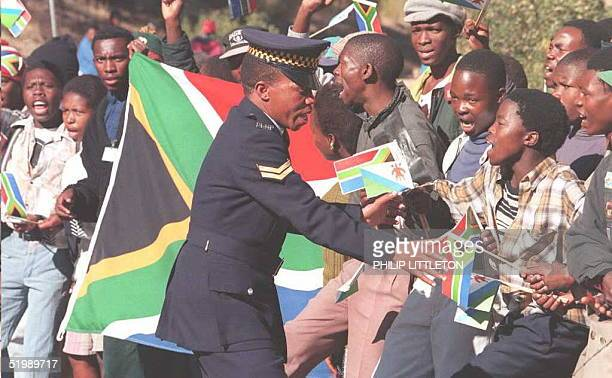 Policeman holds back excited youngsters trying to get a glimpse of South African President Nelson Mandela on his first State visit to Leshoto, 12...