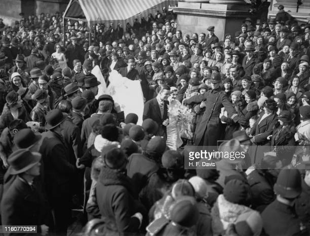 Policeman holds back the crowds as Margaret Whigham and Charles Sweeny leave the Brompton Oratory after their wedding, London, 21st February 1933....