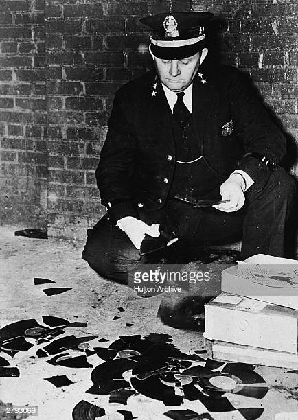 Policeman holds pieces of records that were branded obscene by the police department and smashed Memphis Tennessee February 8 1948