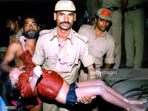 A policeman holds the dead body of a girl whose corpse was retrieved 27 August 1999 from an abandoned reservoir in the southern Indian state of...