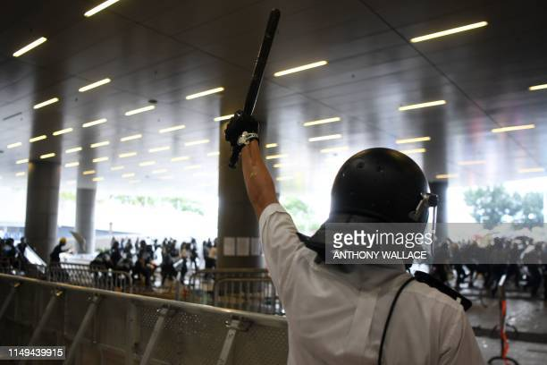 A policeman holds up a baton as protesters storm the Legislative Council building during a rally against a controversial extradition law proposal in...