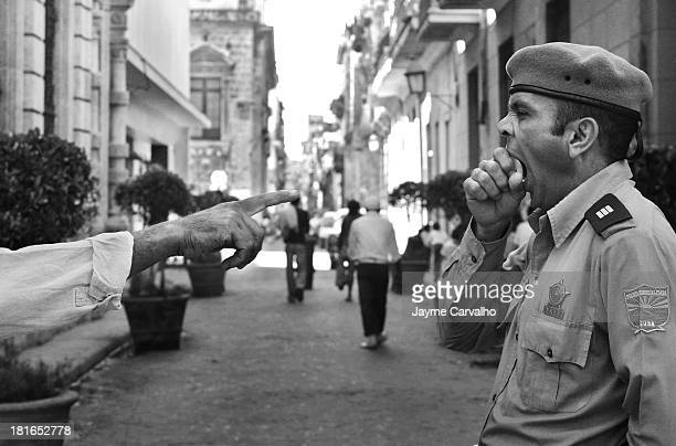 CONTENT] A policeman in a funny scene during a conversation in Old Havana Cuba Dec 2005
