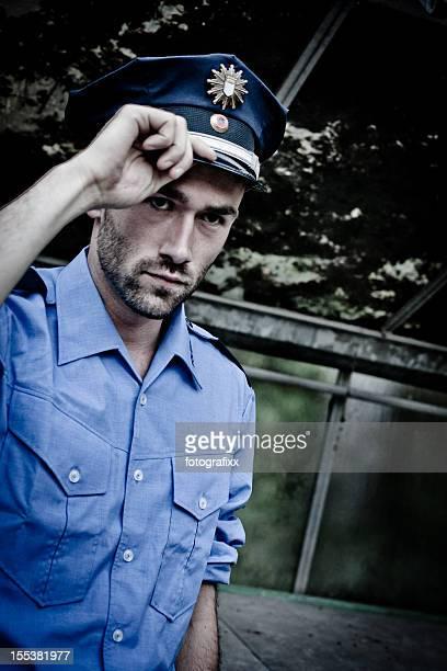 Polizisten in blauer uniform Begrüßung mit seiner hand auf der Kappe