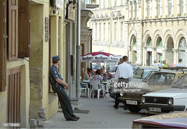 Policeman in front of a pavement cafe in Vilnius Lithuania